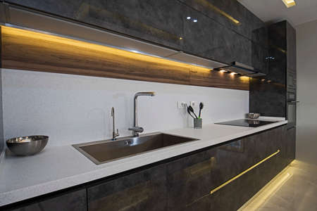 Interior design decor showing modern kitchen with cupboards and sink in luxury apartment showroom