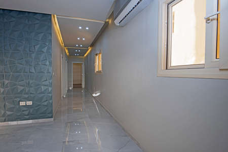 Interior design of a corridor inside a luxury modern apartment building with led strip lighting