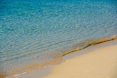 Closeup view across an empty sandy tropical beach shoreline to the open ocean