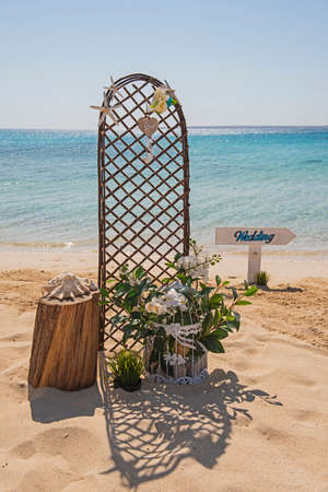 Closeup of wedding sign and decorations on tropical island sandy beach paradise with ocean in background