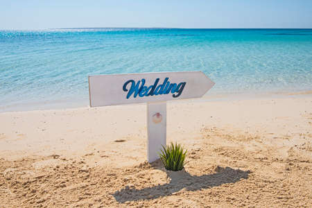 Closeup of wedding sign on tropical island sandy beach paradise with ocean in background Banco de Imagens