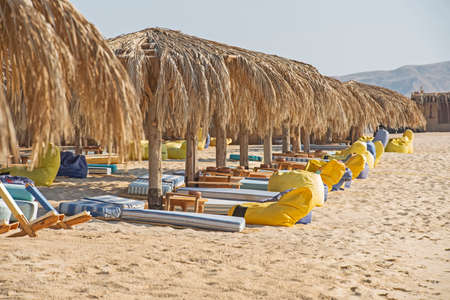 Closeup view across an empty deserted sandy tropical beach with sunbeds and no people