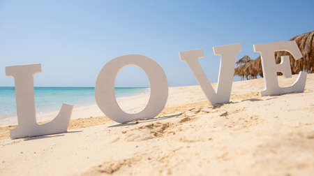 Closeup of romantic love sign on tropical island sandy beach paradise with ocean in background Banco de Imagens