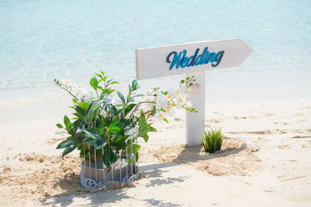 Closeup of wedding sign and plant on tropical island sandy beach paradise with ocean in background