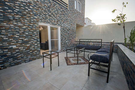 Luxury villa show home with patio and outdoor furniture in sunset