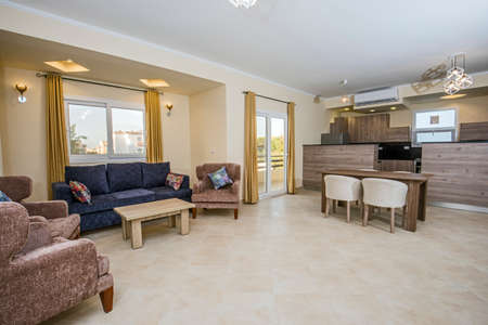 Living room lounge area in luxury apartment show home showing interior design decor furnishing with open plan dining area and kitchen