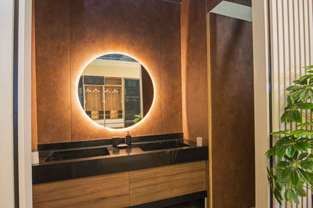 Interior design of a luxury show home bathroom with twin sinks and round mirror
