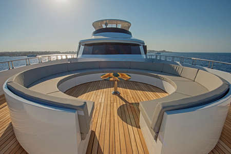 Teak bow deck of a large luxury motor yacht with chairs sofa table and tropical sea view background