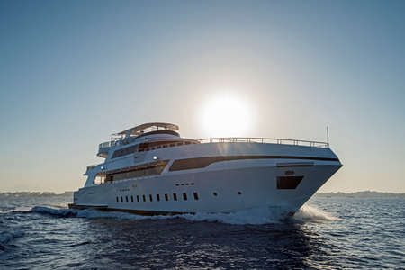 A luxury private motor yacht under way on tropical sea with bow wave at sunset