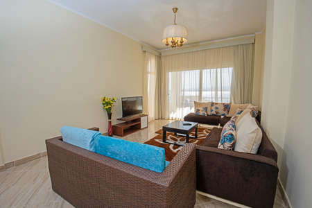 Living room lounge area in luxury apartment show home showing interior design decor furnishing with balcony and sea view