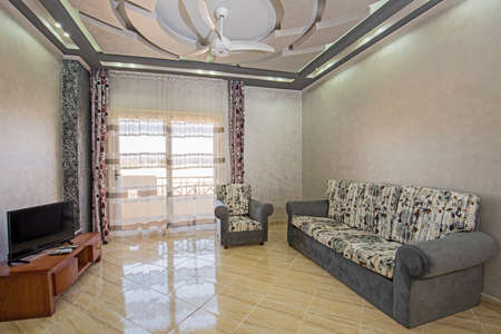 Living room lounge area in luxury apartment show home showing interior design decor furnishing and balcony