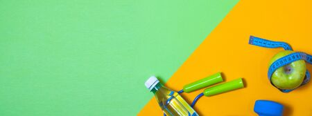 Fitness concept banner with dumbbells, jump ropes and measuring tape on a green and yellow background.