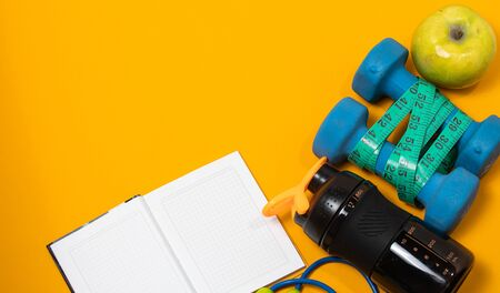 Fitness concept flatlay banner with dumbbells, jump ropes and measuring tape on a yellow background.