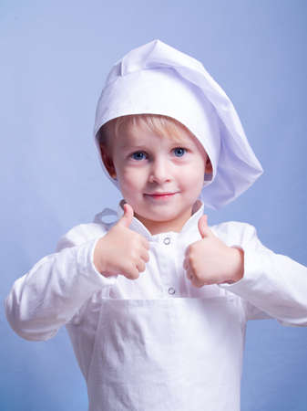 a 3-year-old boy in a suit and a chef's cap smiles at the camera. the little chef shows two thumbs up. the child is happy Stock Photo