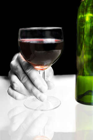 Hand holding red wine glass with bottle Stock Photo - 4321827