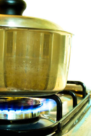 Silver cooking pot in use on a gas stove photo
