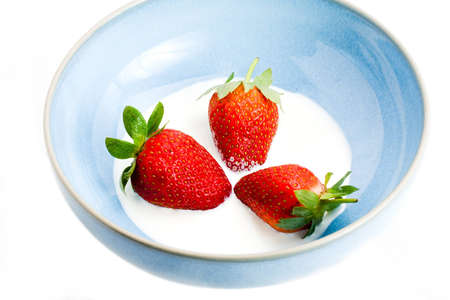 three leafed: Three fresh leafed strawberries in a bowl of cream