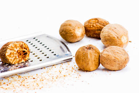grater: Several nutmegs with grater and fresh shavings
