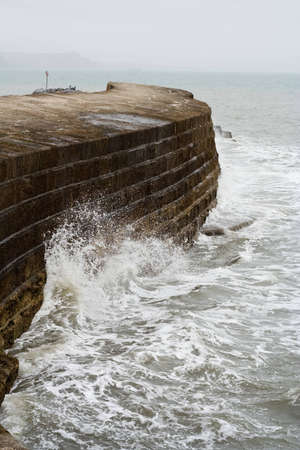 lyme: Waves crashing on a sea wall in Lyme Regis Stock Photo