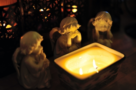 Three angels sitting around a candle