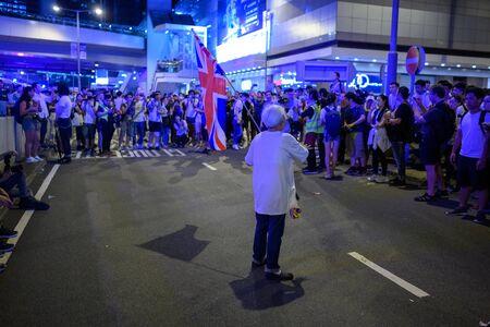 HONG KONG - June 9, 2019: Hong Kong June 9 protest. Old women waving UK flag. Editorial
