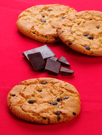 morsels: Round cookies with chocolate on the red table.