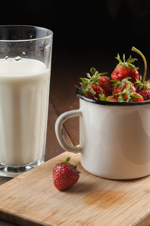 Ripe strawberries in an enamel cup with glass of milk