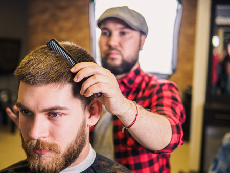 Adult male barber and customer in shop. Beard and hairstyle