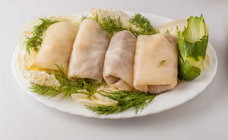 filled roll: Stuffed cabbage with green and carrot on the plate.