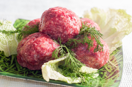minced meat balls on the plate with greens.