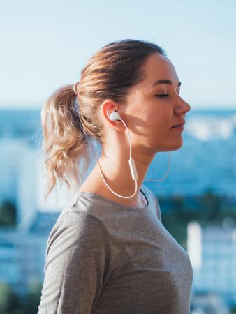 젊은 여자의 귀에 무선 헤드폰입니다.