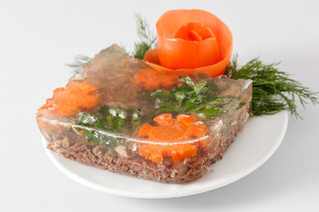 manjar: Russian aspic jelly with greens on a white plate.