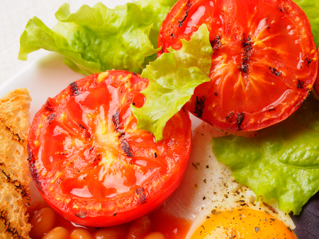 grilled tomatoes in full English Breakfast. macro. Stock Photo