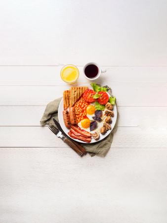 Café da manhã inglês completo incluindo salsichas, tomates grelhados e cogumelos, ovo, bacon, feijão cozido, pão com suco de laranja. Copiar espaço Foto de archivo - 85320318