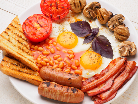 Full English Breakfast including sausages, grilled tomatoes and mushrooms, egg, bacon, baked beans, bread with orange juice.