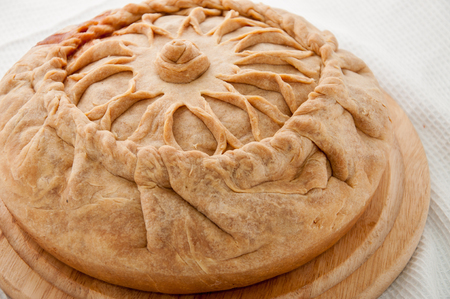Tatar round pie on the table with napkin.