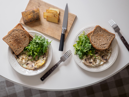Omelette eggs with mushrooms and arugula. Breakfast with cheese and bread. Zdjęcie Seryjne