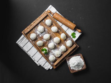Frozen raw dumplings on the wooden desk on black background. Stock Photo