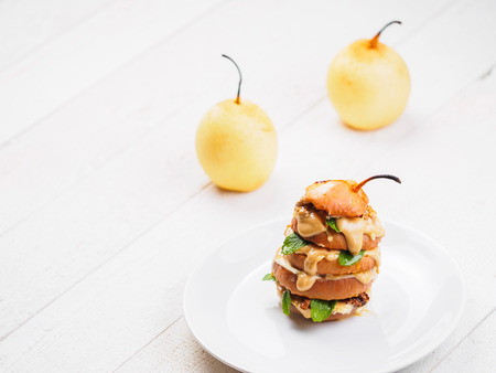 Sliced baked pear with peanut butter on white background.