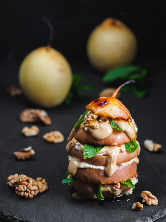 Sliced baked pear with peanut butter on black background.