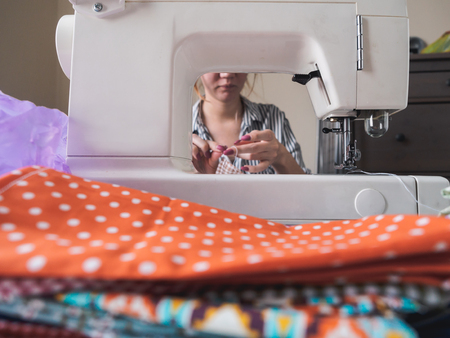 Girl working on sewing machine with textile napkins.