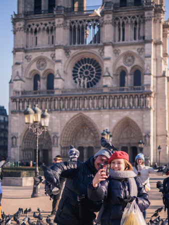 PARIS, FRANCE - JANUARY 20, 2017: Tourists feeding pigeons in the square in front of the cathedral of Notre Dame. Paris, France.