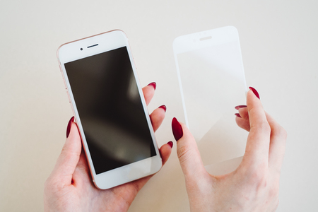 Smartphone with screen protect glass cover in hands. White background.