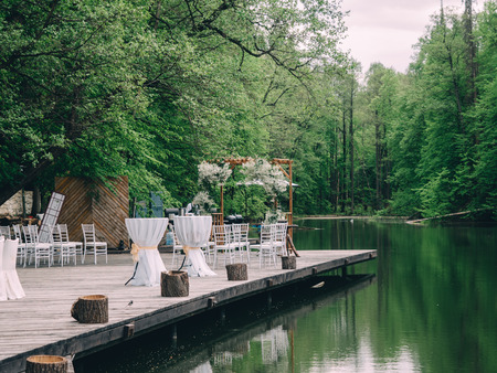Romantic rustic wedding ceremony near river. White wooden chairs and flower arch. Archivio Fotografico