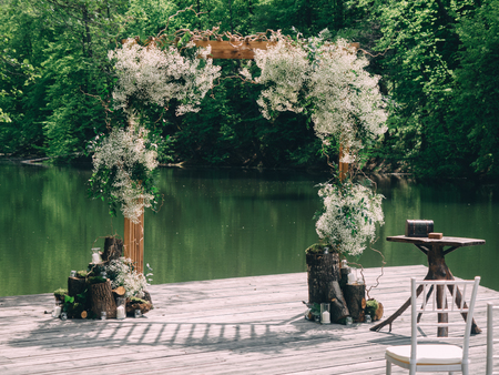 Romantic rustic wedding ceremony near river. White wooden chairs and flower arch. Banco de Imagens