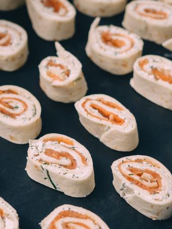 Rolls of thin pancakes with smoked salmon, horseradish cream cheese.