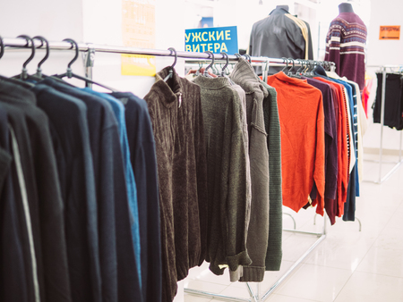 Young woman is browsing a rail of clothes at mall store.