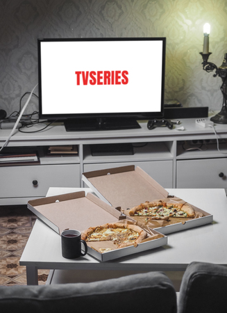 Pizza in delivey box with TV series in living room. Stockfoto