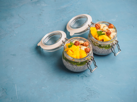 Chia seed pudding in jar with coconut milk, mango and nuts.