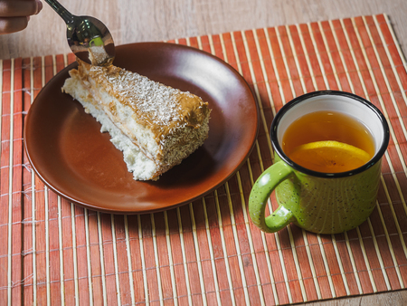 Caramel piece of cake with coconut flakes and lemon tea.